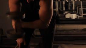 Muskulös kroppsbyggaregrabb som gör övningar med hantlar i idrottshall lager videofilmer