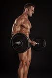 Muskulös kroppsbyggaregrabb som gör övningar med stor hanteldumbb Arkivbilder