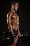 Muskulös kroppsbyggaregrabb som gör övningar med stor hanteldumbb Royaltyfri Bild