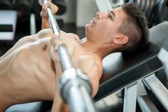 Muskulös kroppsbyggaregrabb som gör lyftande vikt, medan utarbeta royaltyfri fotografi