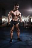 Muskulös kroppsbyggareman för idrottsman nen som poserar med hantlar i idrottshall royaltyfri bild
