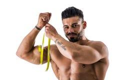 Muskulös kroppsbyggareman som mäter låret med måttband Royaltyfri Bild