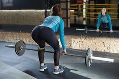 Muskulös kvinna i en idrottshall som gör deadlift Fotografering för Bildbyråer