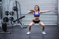 Muskulös kvinna som övar med kettlebell royaltyfria bilder