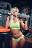Muskulös kvinna som dricker sportnäring Arkivbild