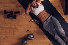 Muskulös kvinna som gör absgenomkörare i idrottshall Arkivfoton