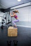 Muskulös kvinna som gör banhoppningsquats arkivfoto