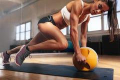Muskulös kvinna som gör intensiv kärnagenomkörare i idrottshall Royaltyfria Bilder
