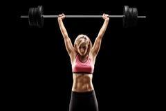 Muskulös kvinna som lyfter en tung skivstång Royaltyfri Bild