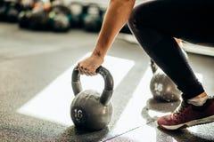Muskulös kvinna som rymmer på den gamla och rostiga kokkärlklockan till idrottshallgolvet royaltyfri bild