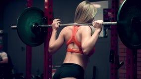 Muskulös kvinna som utarbetar i idrottshalllyftande vikterna arkivfilmer