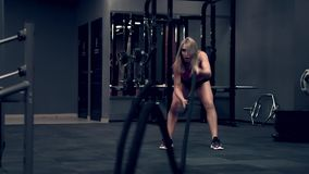 Muskulös kvinna som utarbetar i idrottshalllyftande vikterna