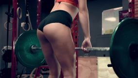 Muskulös kvinna som utarbetar i idrottshalllyftande vikterna lager videofilmer