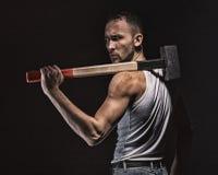 Muskulös man för förvånad brunett med hammaren Arkivfoto