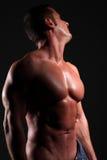 Muskulös man för stående på svart bakgrund Fotografering för Bildbyråer