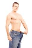 Muskulös man för viktförlust i ett stort par jeans Arkivfoto