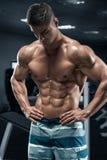 Muskulös man i idrottshallen, abs som utarbetar Stark manlig naken torso, format buk- arkivbild