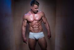 Muskulös man i vita boxarekortslutningar som ner ser royaltyfri bild