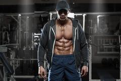 Muskulös man med bröstkorgen och abs för öppet omslag den avslöjande i idrottshallen, genomkörare Arkivbilder