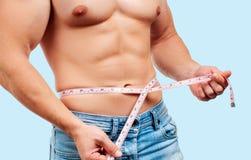 Muskulös man med den perfekta kroppen som mäter hans midja arkivbild