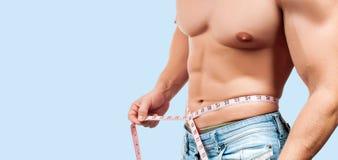 Muskulös man med den perfekta kroppen som mäter hans midja fotografering för bildbyråer