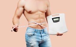 Muskulös man med den perfekta kroppen som mäter hans midjakroppsbyggare med sex packe royaltyfri fotografi