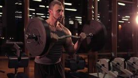 Muskulös man med en skivstång i idrottshallen stock video