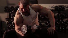 Muskulös man med hantlar i hand som övar i konditionklubba lager videofilmer