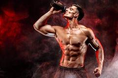 Muskulös man med proteindrinken i shaker royaltyfria bilder