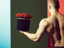 muskulös man med rosor royaltyfria bilder