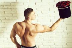 muskulös man med rosor arkivfoto