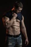 Muskulös man med skjortan på skuldra fotografering för bildbyråer