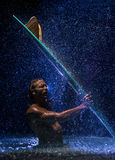 Muskulös man och surfingbräda i vatten Royaltyfri Fotografi