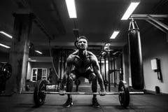 Muskulös man på en crossfitidrottshall som lyfter en skivstång Arkivfoton