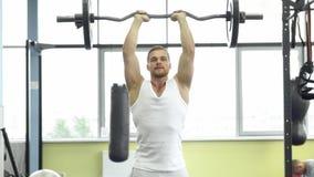 Muskulös man på styrkautbildning i idrottshallen Idrottsman nen gör tricepsövning med en skivstång royaltyfri fotografi