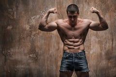 Muskulös man på väggbakgrund Naken torso, abs Royaltyfri Fotografi