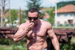 Muskulös man som äter pannkakor royaltyfri foto