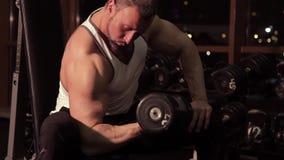 Muskulös man som övar i konditionklubba stock video