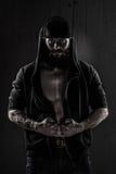 Muskulös man som bär en baseballmössa och en svartblus Arkivfoton