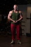 Muskulös man som böjer muskler i idrottshall Royaltyfri Bild