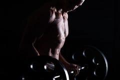 Muskulös man som gör att lyfta för vikt i konditionmitt arkivfoton