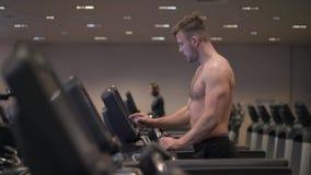 Muskulös man som gör cardio utbildning på trampkvarnen i sund klubbaultrarapid arkivfoton