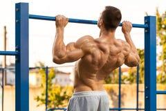 Muskulös man som gör handtag upp på horisontalstången som utarbetar Stark konditionman som drar upp och att visa tillbaka, utomhu royaltyfri fotografi