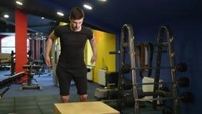 Muskulös man som gör satt övning för ask i idrottshall arkivfilmer