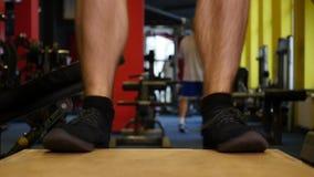 Muskulös man som gör satt övning för ask i idrottshall stock video