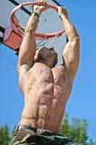 Muskulös man som hänger från basketcirkeln arkivfoto