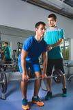 Muskulös man som lyfter Deadlift i idrottshallen med instruktören Royaltyfri Bild