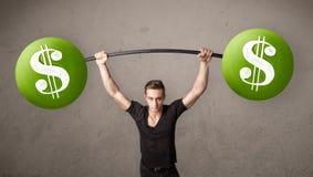 Muskulös man som lyfter gröna vikter för dollartecken fotografering för bildbyråer