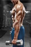 Muskulös man som poserar i idrottshallen som visar triceps Starka manliga nakna torsoabs som utarbetar, fokuserar på handen Royaltyfri Bild