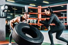 Muskulös man som skjuter en lastbuss i idrottshallen den kvinnliga lagledaren uppmuntrar sportgrabben begreppsmotivation som över arkivbilder